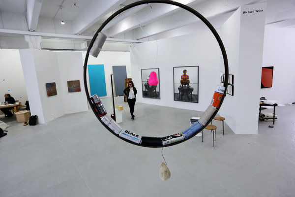Photographs by Dan Finsel from the Richard Telles gallery as seen through a sculpture by Jack Lavender, from the London gallery the Approach. Credit Linda Rosier for The New York Times